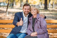 The guy with a smile hugs my mother in an autumn park on a bench. The guy with a smile is holding his thumb up. Hugs mommy with a smile in a purple coat in an Royalty Free Stock Photography