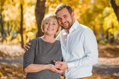 A guy hugs a happy mother in an autumn park. A guy with a smile in a white shirt hugs a happy mother with a beautiful smile in an autumn park Stock Photography