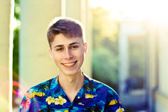 Guy smiling. Young man in hawaiian shirt smiling in sunlight, outdoors. Blurred background Royalty Free Stock Photo