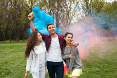 Guy with smoke flare and girls. Handsome guy holding flare producing blue smoke in air posing with two girls in park Royalty Free Stock Image