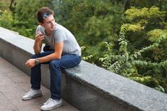 The guy smokes a cigarette sitting on a granite curb. Close his eyes. Royalty Free Stock Photography