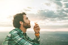 Guy smoking a cigarette. Guy dressed casual and with a beard stock photo