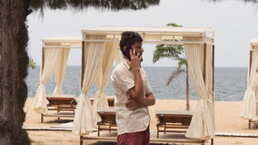 Guy speaks over phone on beach against sunbeds under tents. Guy in white shirt speaks over phone on beach against sunbeds under tents near palm tree stock footage
