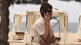 Guy speaks over phone on beach against sunbeds under tents stock video