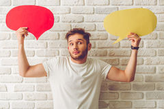Guy with speech bubble. Handsome guy in casual clothes is holding speech bubbles, looking at camera and showing dismay, on white brick wall background stock images