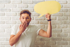 Guy with speech bubble. Handsome guy in casual clothes is holding speech bubble, looking at camera and covering his mouth, on white brick wall background Royalty Free Stock Photography