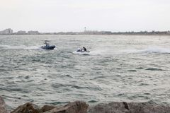 Guy speeding in his jet ski in front of another one Royalty Free Stock Images