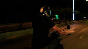 Guy Speeds na motocicleta ao longo da rua do Lit na noite filme