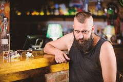 Guy spend leisure in bar with alcohol. Man drunk sit alone in pub. Alcohol addicted concept. Alcoholism and depression. Hipster brutal man drinking alcohol royalty free stock images