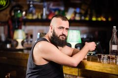 Guy spend leisure in bar with alcohol. Man drunk sit alone in pub. Alcoholism and depression. Alcohol addicted concept. Hipster brutal man drinking alcohol royalty free stock photo