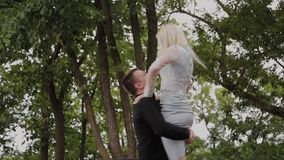 The guy is spinning his girlfriend in his arms in the park. Good mood and laughter. The guy is spinning his girlfriend in his arms in the park. Good mood and stock video footage