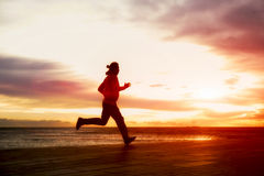Guy with sport beautiful figure running along the  at sunset Stock Images