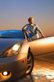 Guy with a sport car. Handsome guy near the modern sport car at sunset time Royalty Free Stock Photography