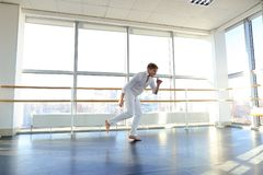 Guy spotting in white suit and raving at studio. Male dancer rejoicing victory at competition at gym. Young person looks fashion in white suit. Concept of Royalty Free Stock Photo