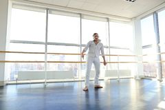 Guy spotting in white suit and raving at studio. Male dancer rejoicing victory at competition at gym. Young person looks fashion in white suit. Concept of Stock Photos