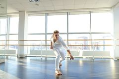 Guy spotting in white suit and raving at studio. Male dancer rejoicing victory at competition at gym. Young person looks fashion in white suit. Concept of Stock Photo