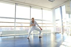 Guy spotting in white suit and raving at studio. Male dancer rejoicing victory at competition at gym. Young person looks fashion in white suit. Concept of Royalty Free Stock Photography