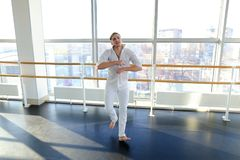 Guy spotting in white suit and raving at studio. Male dancer rejoicing victory at competition at gym. Young person looks fashion in white suit. Concept of Stock Image