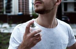 Guy sprays perfume stock photos