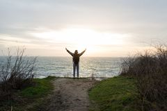 The guy is standing on a cliff and raising his hands up. A young guy with a backpack stands on a cliff above the sea and raised his hands upwards Stock Photos