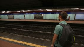 Guy standing on empty platform in underground and waiting for a train to arrive. Stock footage stock video