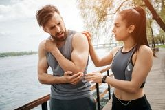 Guy is standing with a girl on a bridge. He has a pain in his elbow. His girlfriend is holding her hand on his shoulder. And worrying about him Stock Images