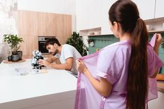 The guy is standing in the kitchen and collecting the robot. The girl stands before him flinging her robe. He does not pay attention to it Stock Photos