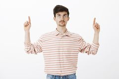 Guy standing still, worrying about falling rocks. Portrait of intense nervous european guy with moustache, raising index. Fingers, looking and pointing up Stock Photos
