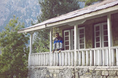 Guy standing on terrace of a cottage in mountain Royalty Free Stock Photography