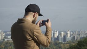 Young man in cap makes a panorama photo of city at smartphone stock video