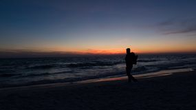 Guy stands in front of dramatic sunset over the ocean royalty free stock photos