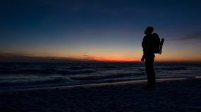 Guy stands in front of dramatic sunset over the ocean royalty free stock images