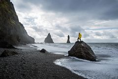 Guy stands on a rock on a black beach in Iceland, the concept of freedom.  royalty free stock images