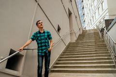 The guy stands on the stairs and thinks about success stock image