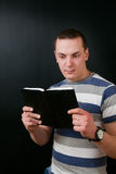Guy stares into a book Stock Images