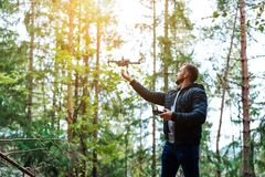 Guy starts a quadrocopter in the forest Royalty Free Stock Images