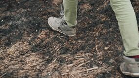 The guy steps on the burnt dry grass. Close-up of the legs