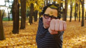 Guy like a superhero stretched out hand with fist forward and flies to the camera in the autumn park. Leaf fall in a. Guy stretched out hand with fist forward stock video