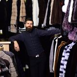 Guy with strict face with furry coats on background. Guy with strict face in front of furry coats on background. Man with beard and mustache in fur shop. Macho stock images