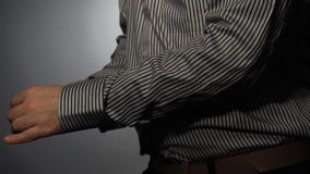 The guy in the striped shirt inserts cufflinks sleeve stock video footage