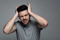 Guy is suffering from hurt. Splitting headache. Portrait of young exhausted bristled man is standing and touching his head while frowning his face from pain royalty free stock photography