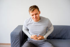 Guy suffering from a stomachache. A portrait of a guy suffering from a stomachache Stock Photos