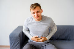 Guy suffering from a stomachache. A portrait of a guy suffering from a stomachache Royalty Free Stock Photo