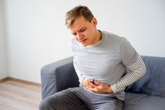 Guy suffering from a stomachache. A portrait of a guy suffering from a stomachache Stock Photography