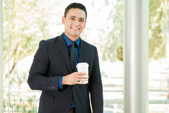 Guy in a suit drinking coffee. Handsome young businessman drinking a cup of coffee and smiling Stock Images