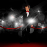 Guy in a suit on the red carpet. Attractive guy in a suit on the red carpet is hiding from the paparazzi flashes Royalty Free Stock Photo