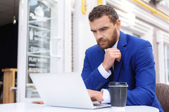 Guy in suit sitting in front of laptop stock image