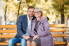 A guy hugs his mom on a bench in an autumn park. A guy in a suit with a smile hugs his smiling with glasses mom on a bench in an autumn park Royalty Free Stock Image