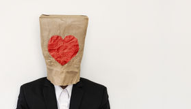 A guy in suit wearing brown paper bag with heath shape Stock Photography