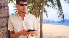 Guy in sunglasses operates iphone under palm tree on sand beach. Young guy in white and sunglasses operates iphone with ear phones under palm tree on sand beach stock video